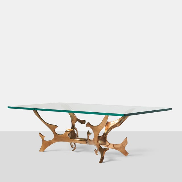 A sculptural table in patinated bronze with a glass top. Signed and numbered.
