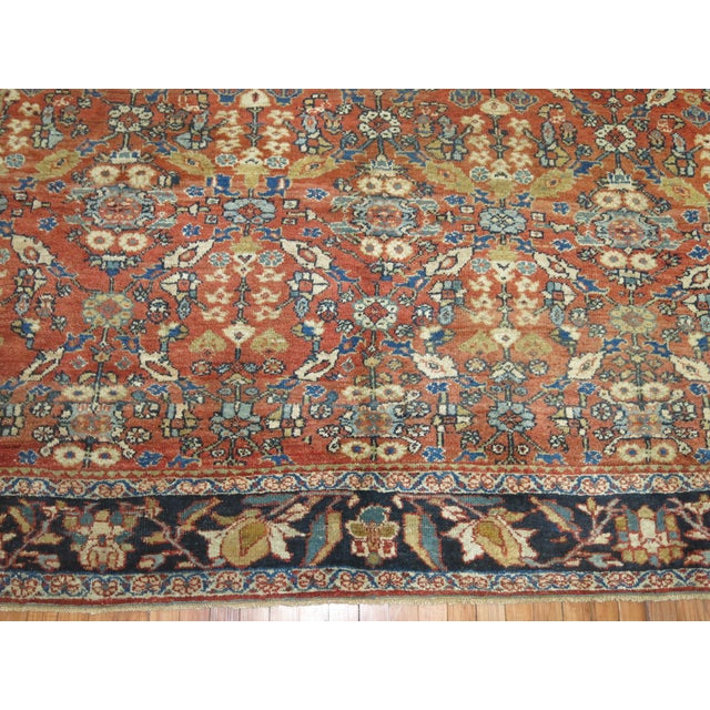 An early 20th century Persian Mahal rug with an all over design in rusty reds and navy blue with great wool and texture....