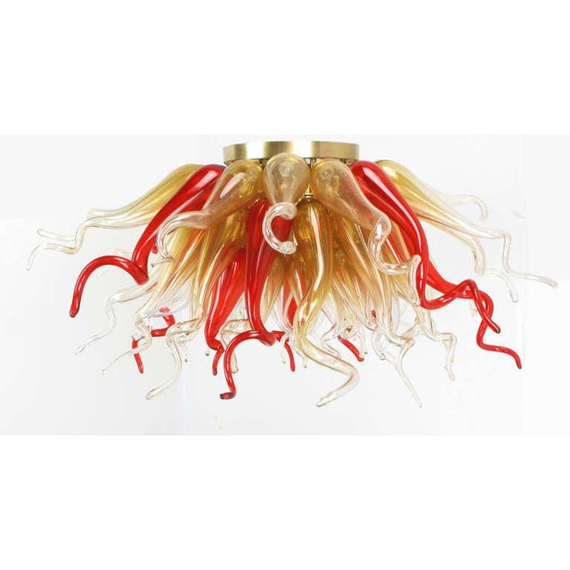"""Sculptural hand blown crimson and gold glass chandelier in the manner of Dale Chihuly. 42"""" in diameter and consisting of..."""