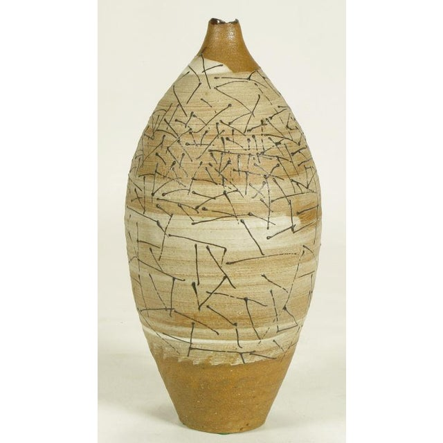Free edge hand thrown terra cotta vase with taupe banded glaze and black glazed abstract detail. From the collection of...