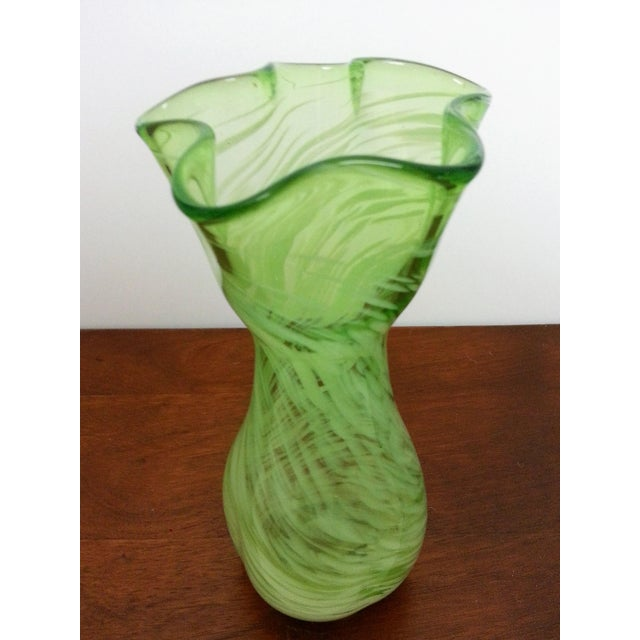 This hand-blown Murano glass vase dances with white swirls against a pale green body. The graceful, undulating top adds...