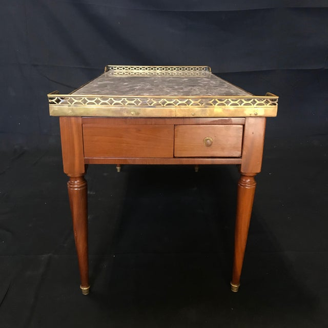 Elegant classic French Louis XVI style coffee table having gold fretwork around a gorgeous gray Italian marble top with...