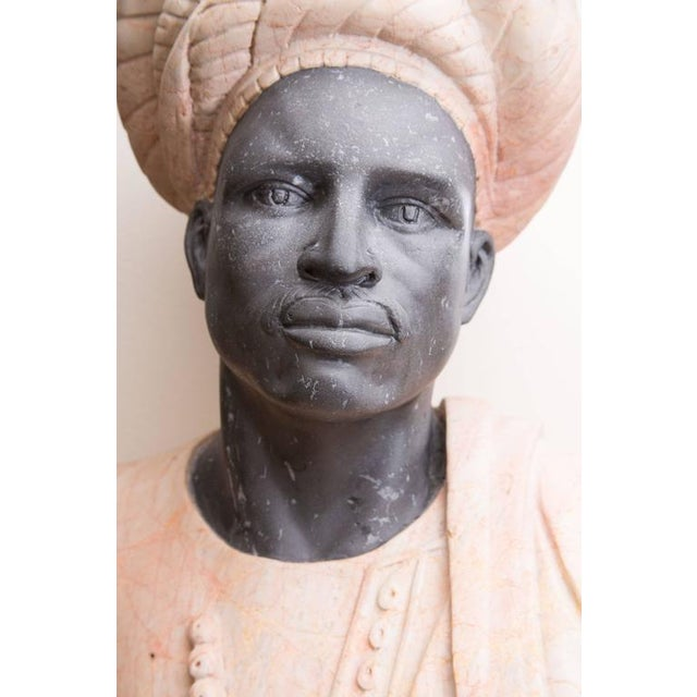 This marble bust of a Moor shows beautiful carved details of a ebony face with native turban and cloak, circa 20th century.