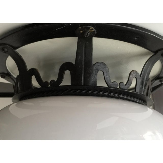 Priced per item. Early 20th century flushmount of forged metal and white glass.