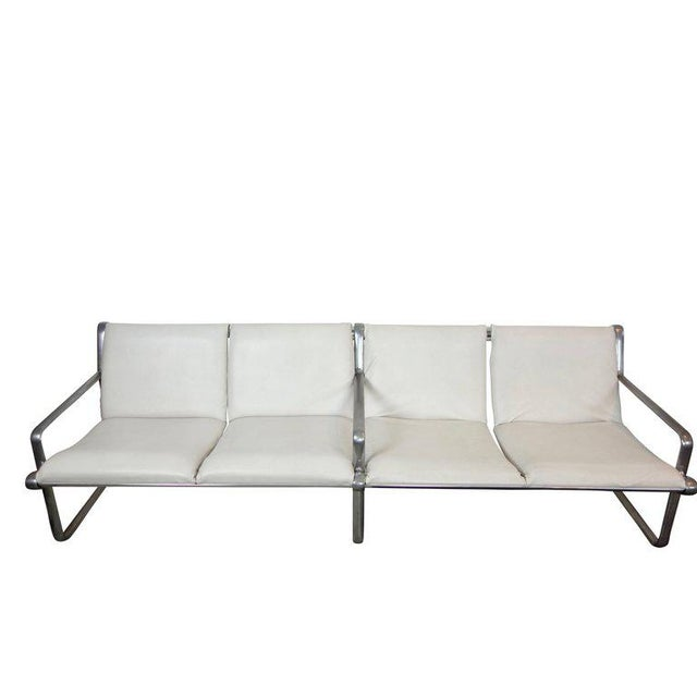 This is a four-seat Hannah and Morrison airport sling sofa produced by Knoll with aluminum frame and white leather...
