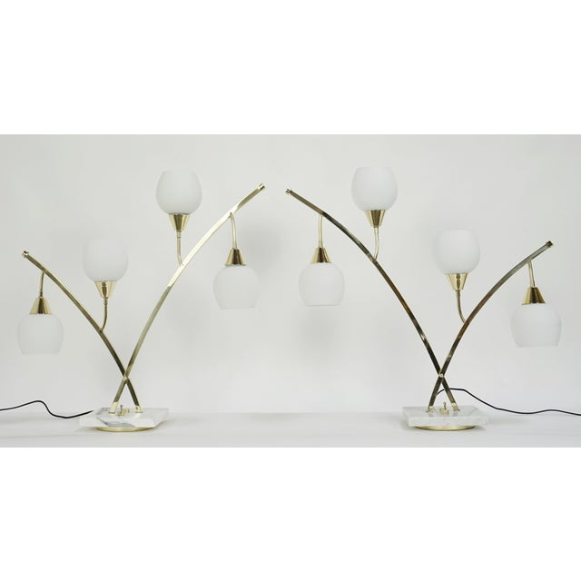 Elegant pair of four light table lamps. Marble bases, polished brass arms and soft white glass shades. Recently buffed and...