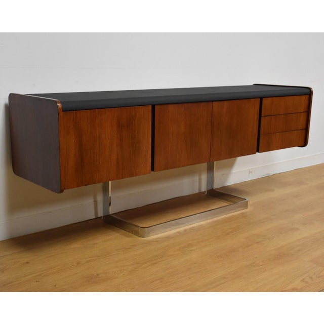 This Ste-Marie and Laurent sideboard has beautiful rosewood grain and a black vinyl top. This mid century credenza floats...