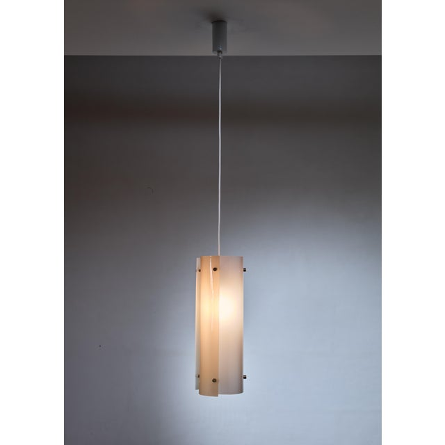 A Yki Nummi model 64-430 pendant lamp for Orno, made of three curved white and soft yellow plexiglass elements, held...