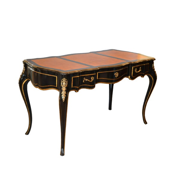 Graceful writing desk by Drexel in ebonized wood and a light brown three part leather top. In the style of Louis XV, comes...