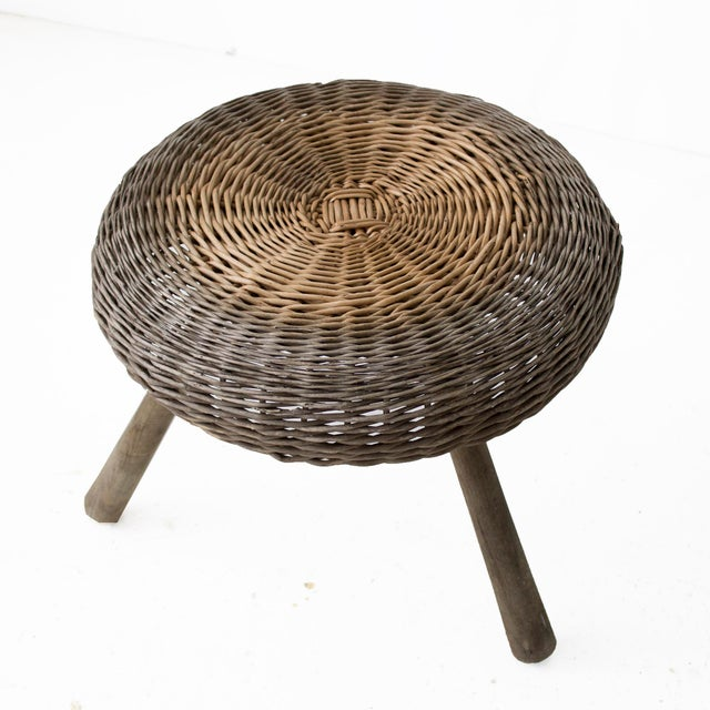 Whimsical small wiicker stool designed by Tony Paul, circa 1950. Weathered walnut legs and wicker seat.