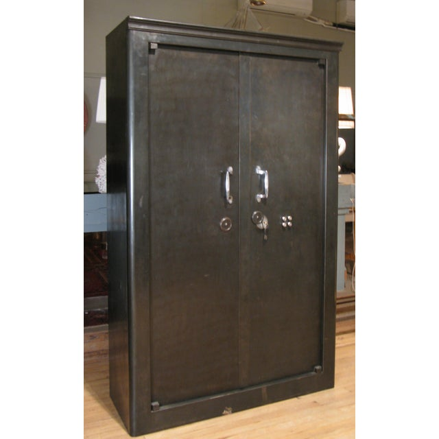 A remarkable antique 1940s French steel locking safe cabinet, restored with a lacquered Chinese red interior. The cabinet...