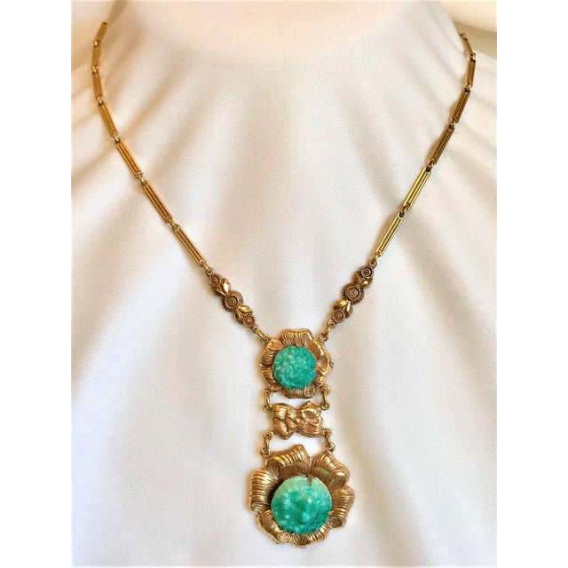 Circa 1930/40s brass floral motif pendant necklace set with jade-green floral molded glass stones and hanging from a brass...