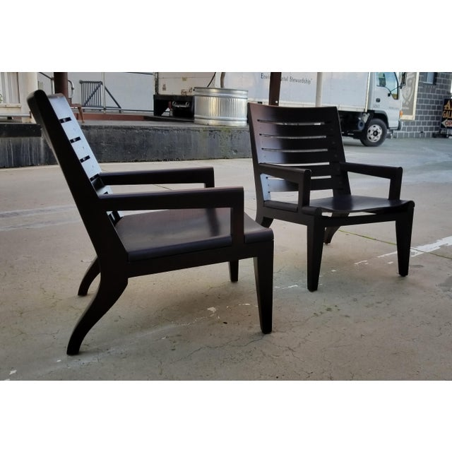 A pair of fine lounge chairs designed by Christian Liaigre for Holly Hunt. Crafted in solid Honduras mahogany with leather...