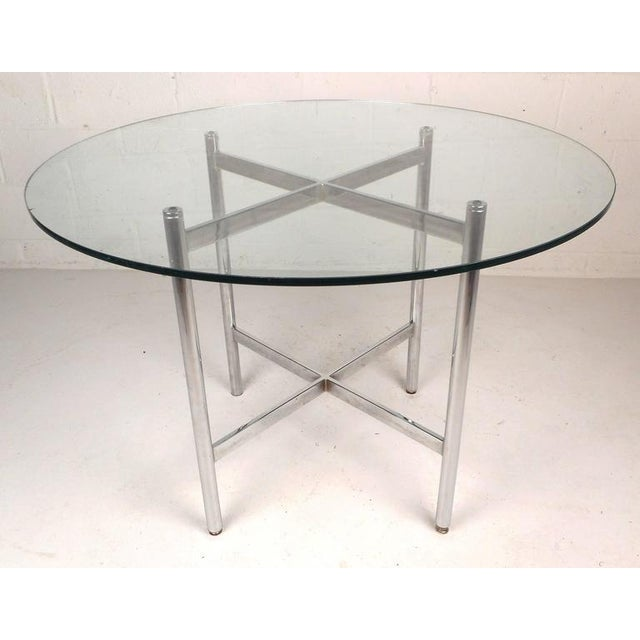 Stunning vintage modern dining set with a table and four-arm chairs. The dining table features a thick round glass top...