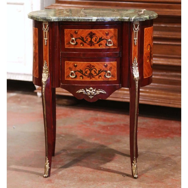 This elegant, kidney-shaped fruitwood antique commode was crafted in France, circa 1980.The commode sits on cabriole legs...