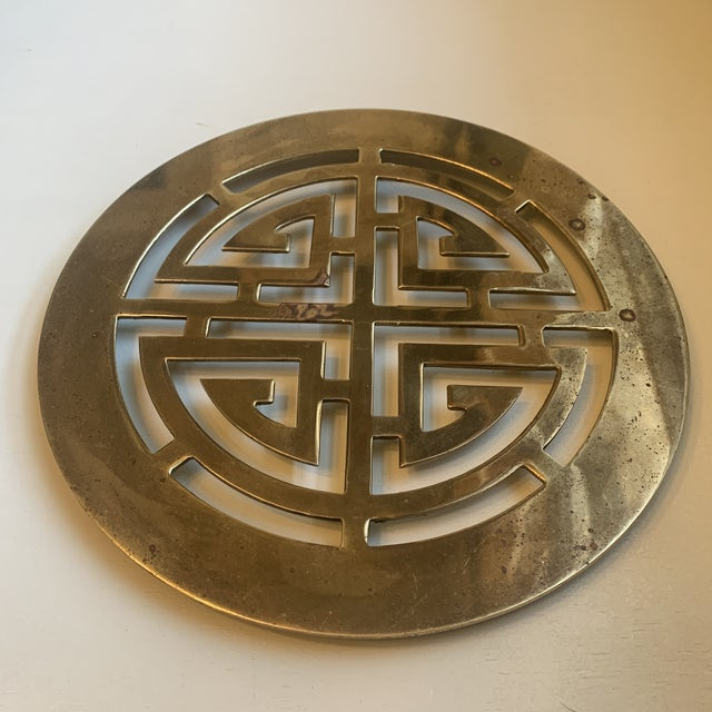 Large, vintage brass trivet with a chinoiserie design and 4 brass feet.