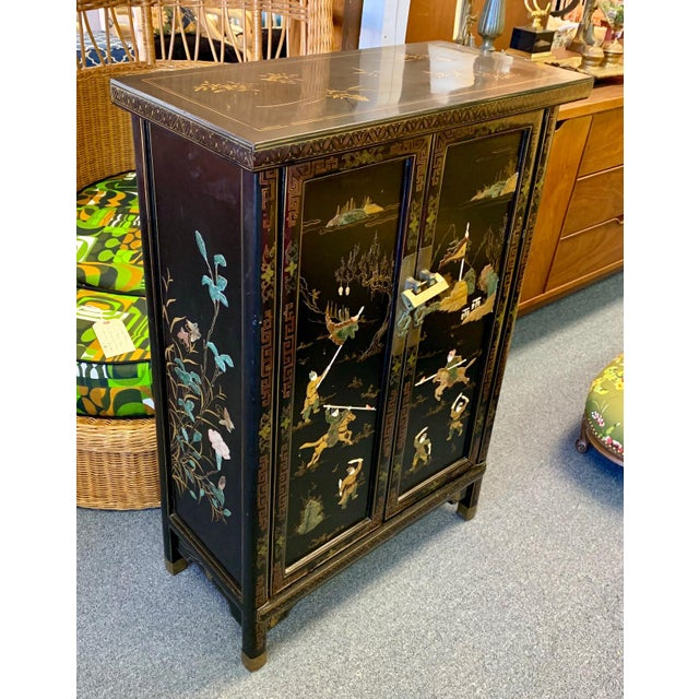 A gorgeous shiny black lacquered Chinoiserie chest on brass-capped legs. Two doors, and one interior shelf, original gold...