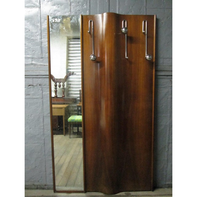 Italian wall-mounted coat rack or hall stand with mirror. Has a waved front.