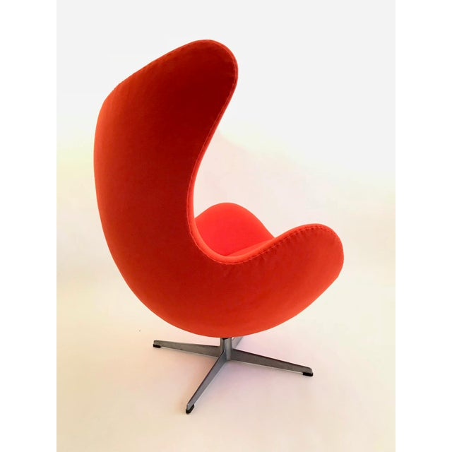 An original model Egg Chair in orange fabric. Properly reupholstered in NOS Vintage Fabric with hand-stitched closing...