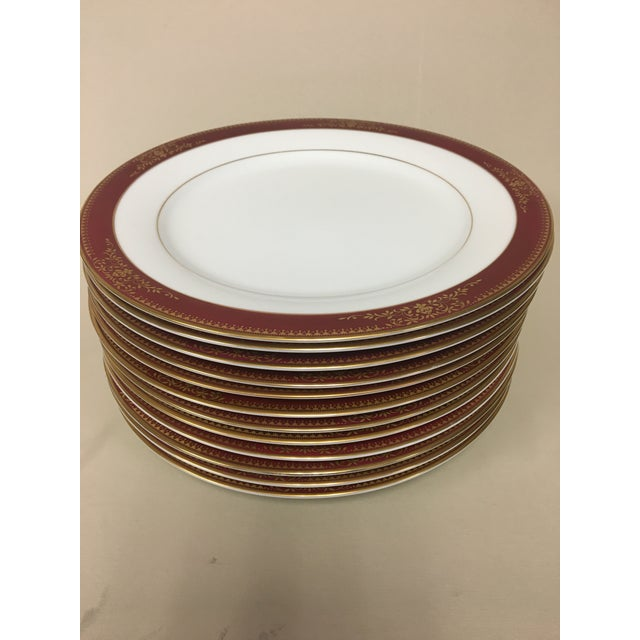 Noritake Goldmere Dinner Plates, Set of 12 features a rich raspberry wine red band with filigree gold details and trim.