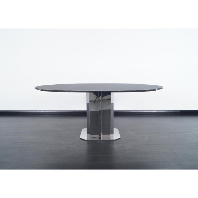 This stunning vintage Italian dining table attributed to Antonia Astori. Features a custom granite top with chrome plated...