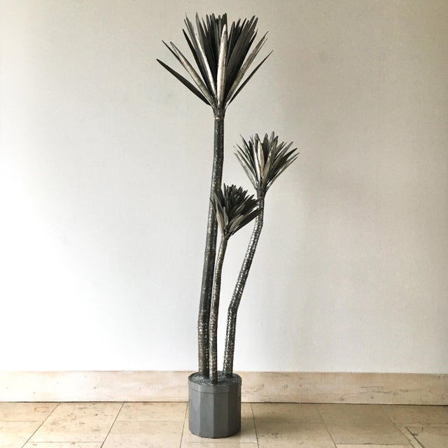 A 1970s Metal Palm Tree Floor Standing Sculpture. Made up of three branches of varying heights and spread with a weighted...