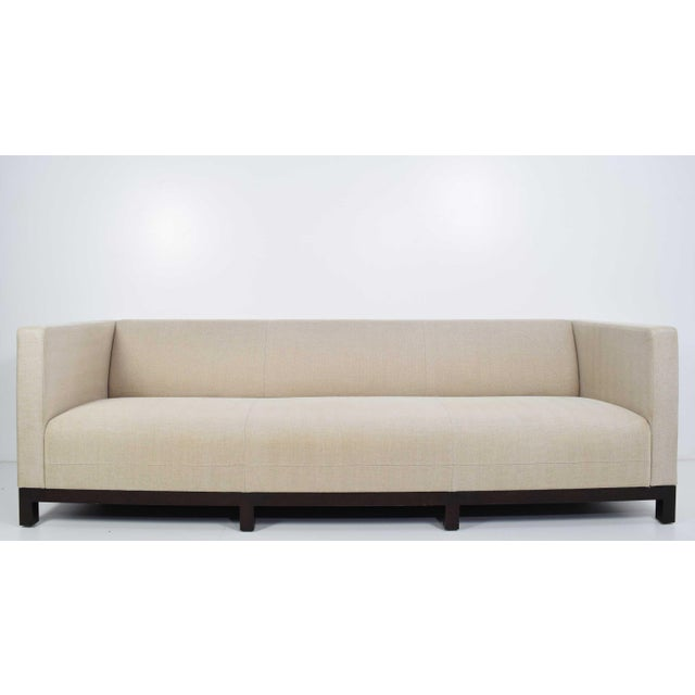 Beautiful sofa is a woven fabric (maybe silk or linen) by Christian Liaigre for Holly Hunt. Has a mahogany base.