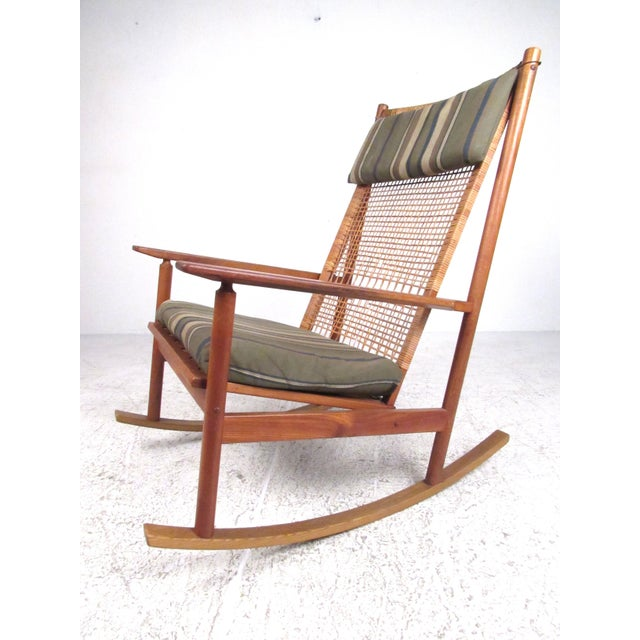 This impressive vintage modern rocking chair features high back teak frame with vintage cane webbing. Added cushion for...