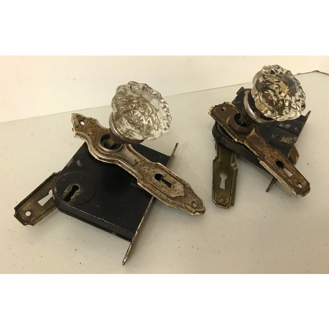 Two vintage door locks. Glass knobs on one side and thumb turn latch on the other.
