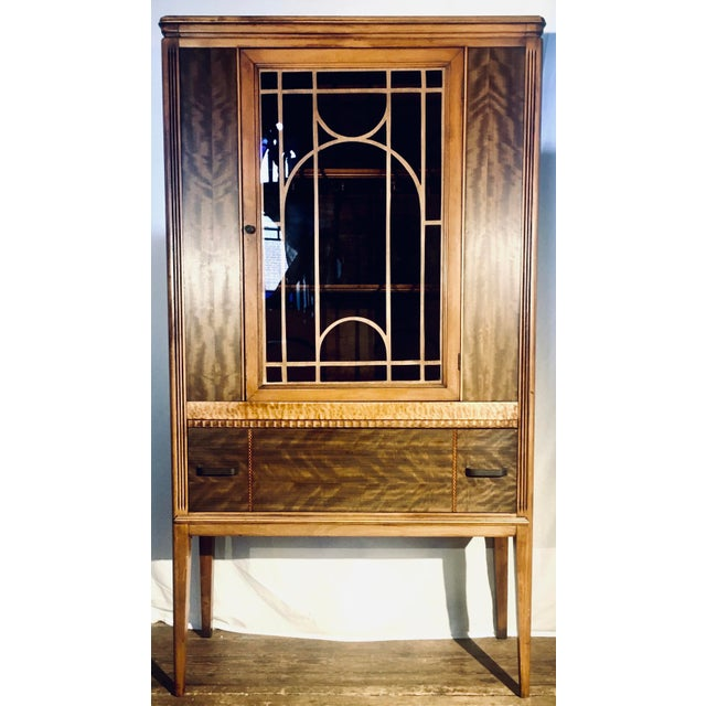 Late 1920s to 1930s streamlined Art Deco china cabinet with walnut and exotic wood veneers. This piece includes a deep...