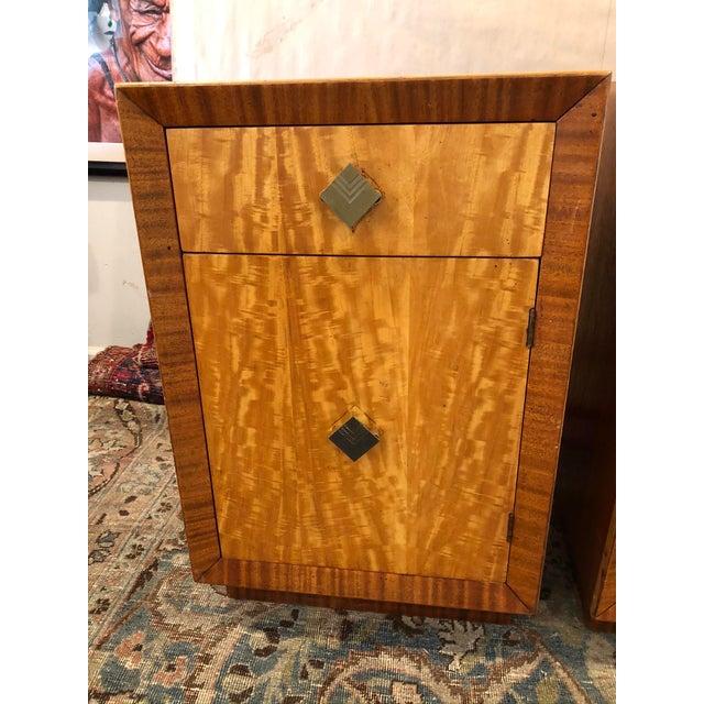 Pair of mid-century art deco nightstands with original harware and stunning wood vaneer. Drawer and door fronts are...
