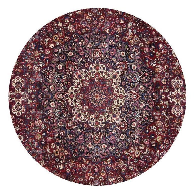 Characterizing the lavish curvilinear style of Art Nouveau, this sublime antique Persian Mashad rug features an ornate...