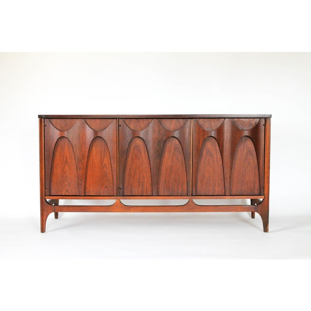 Offered is a Mid-Century modern Broyhill Brasilia three-door credenza. Makers mark stamped on back. Some wear to front foot.