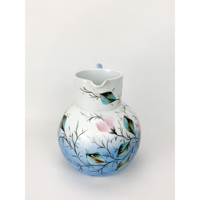 This vintage, authentic porcelain blue pitcher features a lovely pink flower motif.