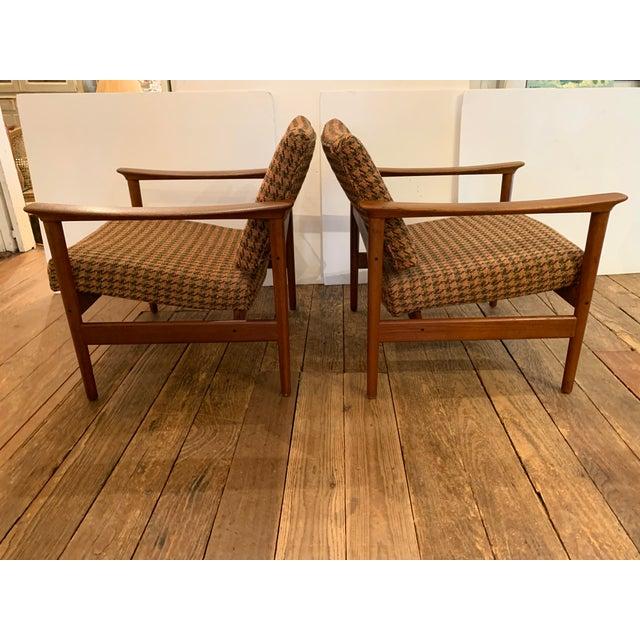 Sophisticated vintage Danish mid century modern club chairs having sleek teak frames, newly restored, and updated wool...