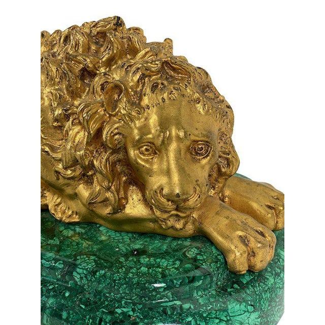 An 1880 Russian bronze dore lion resting on an oval malachite base.