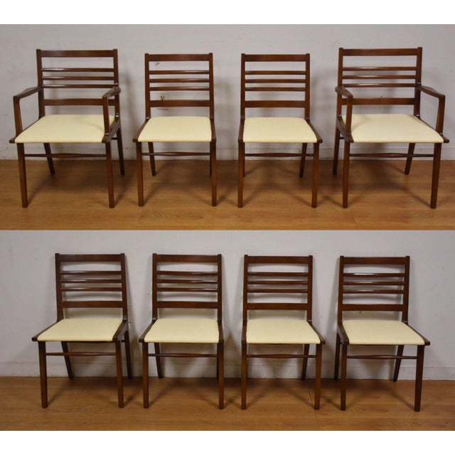 A set of eight mid century modern ladder back dining chairs made by RWAY Furniture. Off white vinyl seats and canted legs....