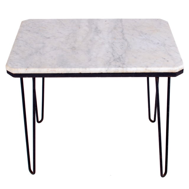 Offered is a carrera marble hairpin table. The slab resting atop wooden base over hairpin legs.