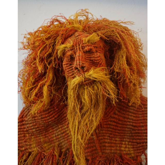 Dyed hemp woven into the shape of a lion or reclining old hippie. Mounted on a wire frame and signed on a wooden bead...