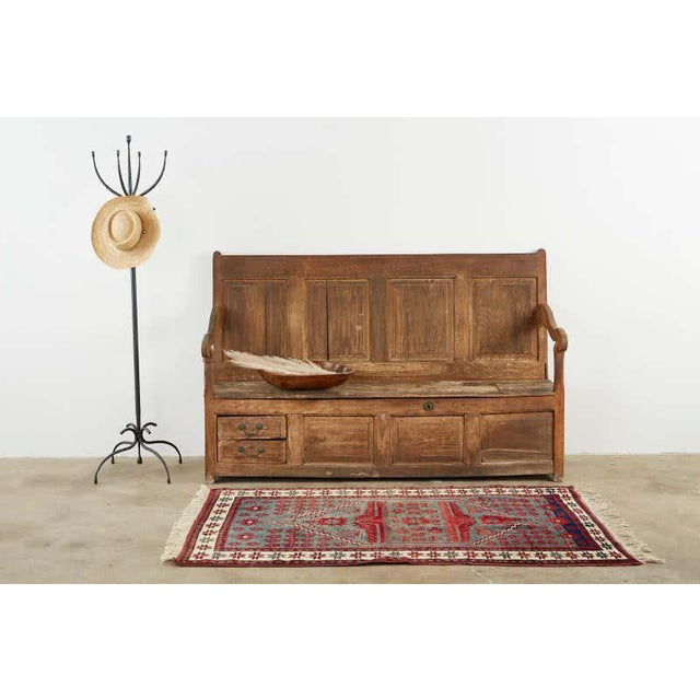 Rustic 19th century English Georgian box settle or hall bench. Crafted from oak featuring a paneled back. The large...