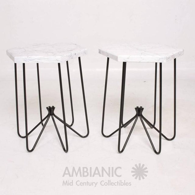 For your consideration a pair of side table after Jean Roeyere. Unmarked. New marble top. Iron base has been re-painted in...