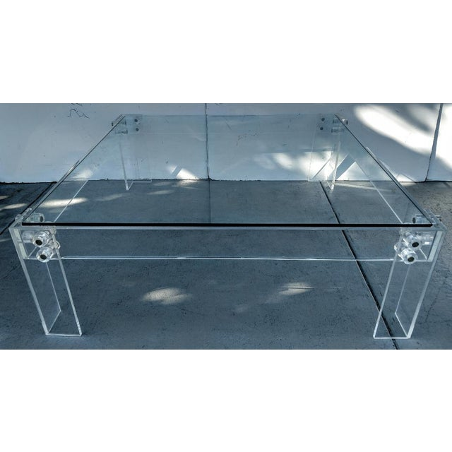 This vintage lucite cocktail table has great industrial lines to it, with its bolted construction and wide panels of...