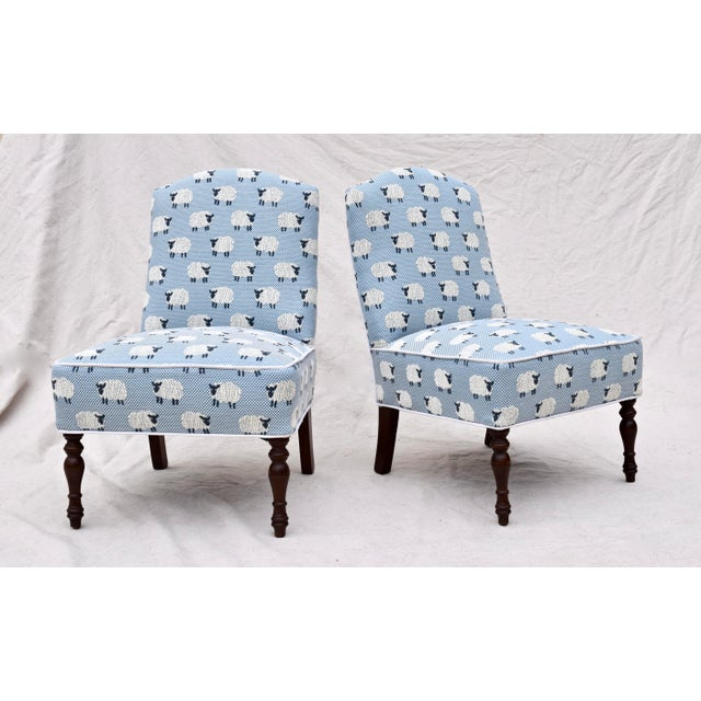 """A pair of antique slipper boudoir chairs with turned mahogany front legs upholstered in Scalamandré """"Ewe Too"""" blue small..."""
