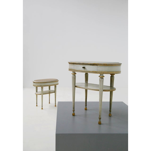 Elegant pair of French style bedside tables of the 50s. The bedside tables are in white lacquered wood with gold painted...