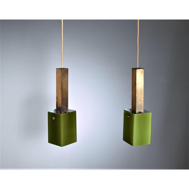 A pair of Italian pendants, made of a rectangular brass stem with a green glass shade hanging from it. The style is...