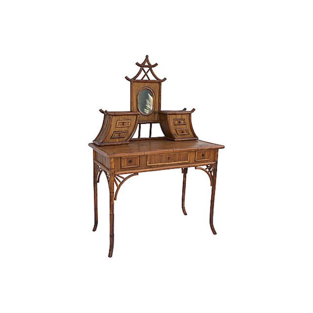 Midcentury chinoiserie rattan vanity featuring seven drawers and a mirror with pagoda crown detail. Top portion has pegs...