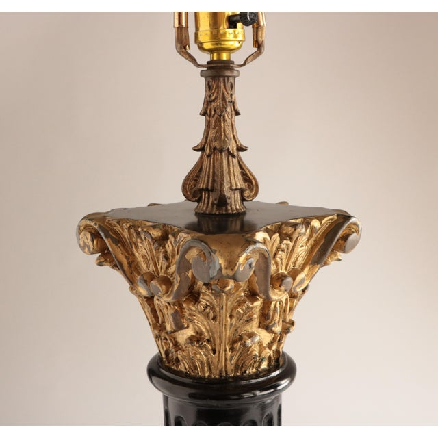 Glossy black column with gilded capital decorated with acanthus leaves and scrolls. Mounted on an acrylic base, this lamp...