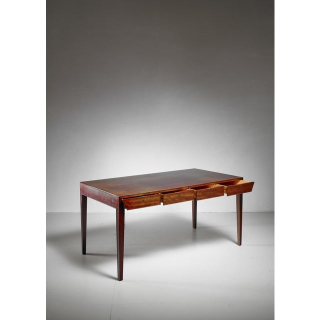 An elegant mahogany deks on tapering legs by Severin Hansen Jr. for Haslev Møbelsnedkeri. The desk has four drawers in...