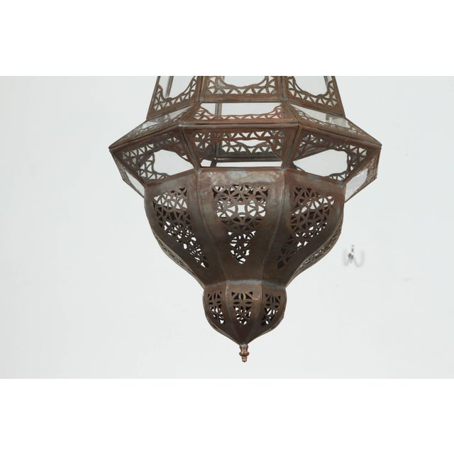Moroccan diamond shape clear glass metal pendant. This light fixture is handcrafted by artisans in Morocco; hand-cut metal...