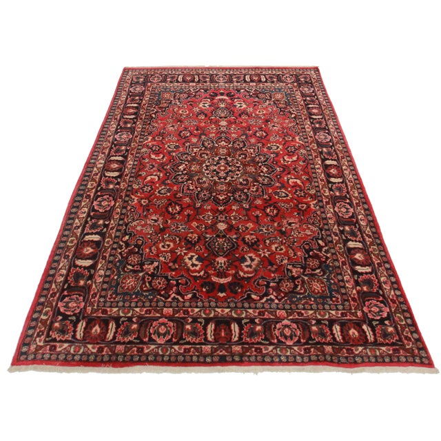Hand Knotted Wool Persian Mashad Rug. Floral design. Red border with red and blue background.